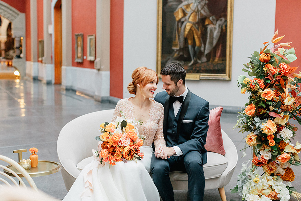 bride in a white ballgown with a crystal bodice and long sleeves with her hair in a low bun and the groom in a navy shawl lapel tuxedo with a black satin lapel sitting on a white couch