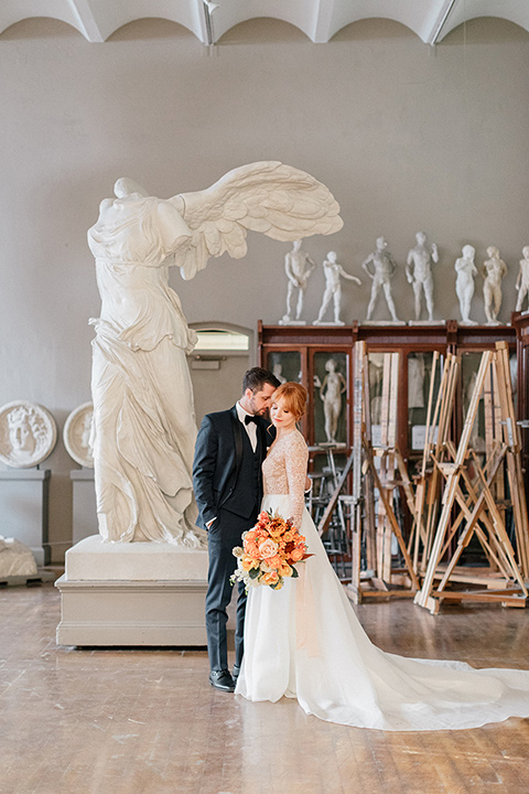 bride in a white ballgown with a crystal bodice and long sleeves with her hair in a low bun and the groom in a navy shawl lapel tuxedo with a black satin lapel near ancient sculptures