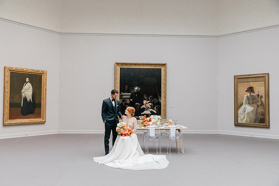 bride in a white ballgown with a crystal bodice and long sleeves with her hair in a low bun and the groom in a navy shawl lapel tuxedo with a black satin lapel sitting in the reception hall space