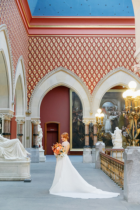bride in a white ballgown with a crystal bodice and long sleeves with her hair in a low bun standing in the museum