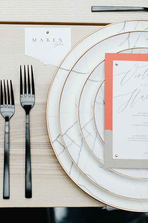 white plates and black flatware on a light wood style table