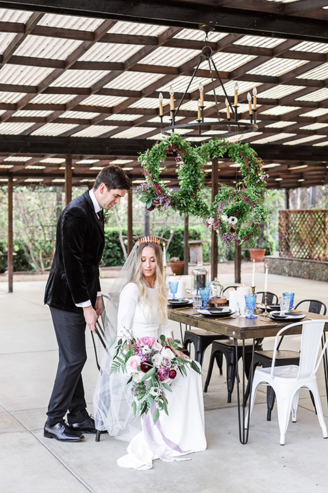 bride in a white lace gown and long sleeves and the groom in a black velvet tuxedo and a black long tie sitting together at the sweetheart table