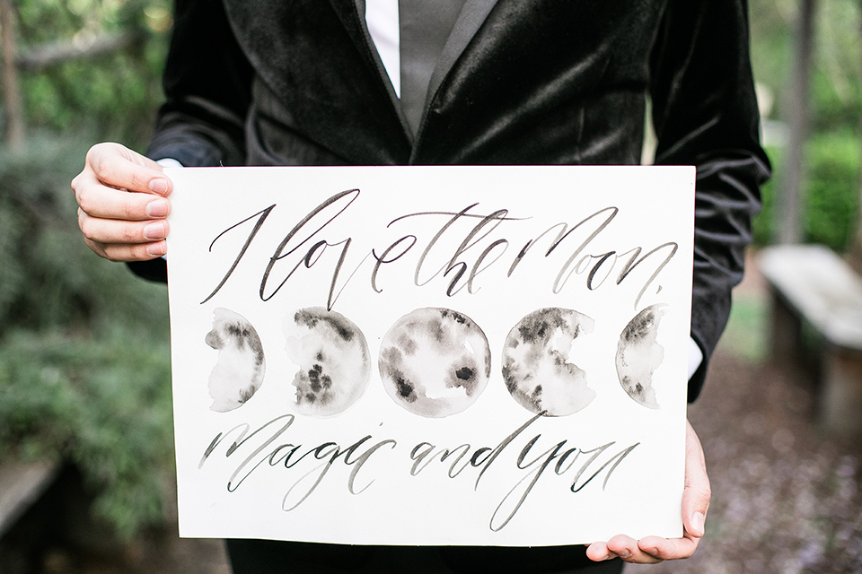 groom holding a welcome to the wedding sign
