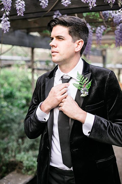 the groom in a black velvet tuxedo and a black long tie