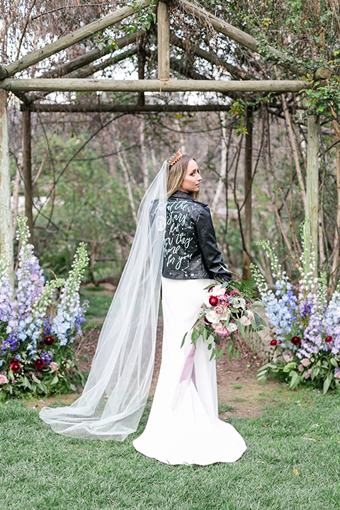 bride in a white lace gown and long sleeves and a leather jacket