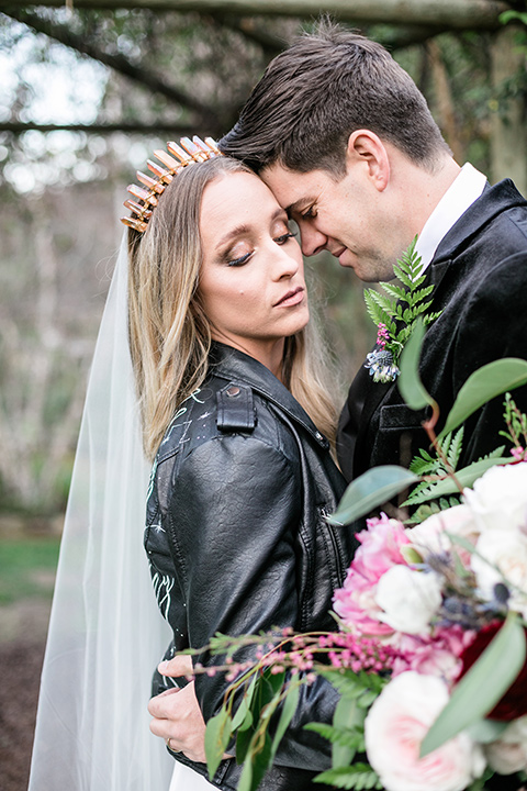 bride in a white lace gown and long sleeves and the groom in a black velvet tuxedo and a black long tie sitting together at the sweetheart table together close up