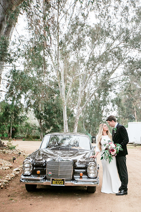 bride in a white lace gown and long sleeves and the groom in a black velvet tuxedo and a black long tie by a vintage car