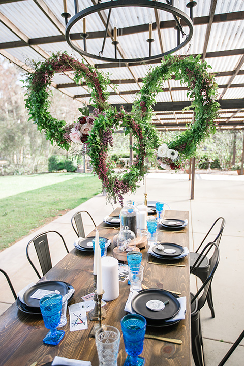 wooden table design with royal blue linens and circular floral hedges overhead