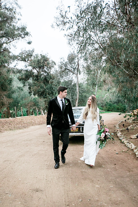 bride in a white lace gown and long sleeves and the groom in a black velvet tuxedo and a black long tie walking down the street together