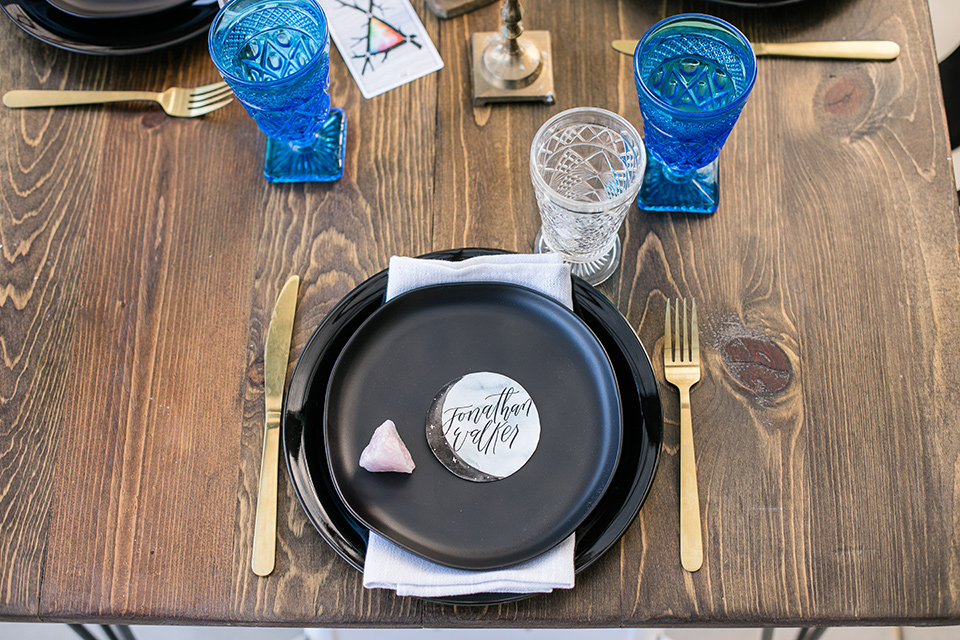 black plate design with gold flatware and royal blue drinkware