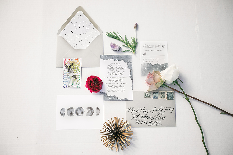 white invitations with calligraphy and a small floral design