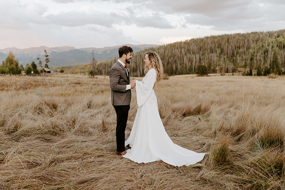 bride in a white lace gown with long flowing sleeves and high neckline with the groom in a café brown suit coat and blue pants with a gold velvet bow tie, exchanging vows in the fields