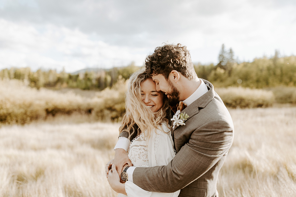 bride in a white lace gown with long flowing sleeves and high neckline with the groom in a café brown suit coat and blue pants with a gold velvet bow tie in an embrace