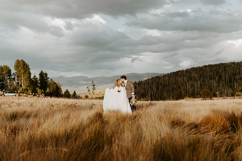 bride in a white lace gown with long flowing sleeves and high neckline with the groom in a café brown suit coat and blue pants with a gold velvet bow tie in an embrace in the fields
