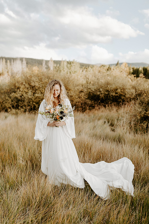 bride in a white lace gown with long flowing sleeves and high neckline