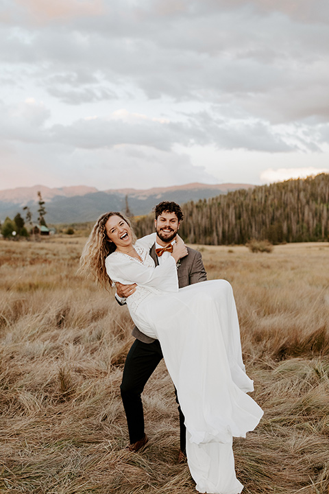 bride in a white lace gown with long flowing sleeves and high neckline with the groom in a café brown suit coat and blue pants with a gold velvet bow tie, groom spinning bride in his arms