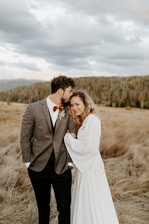 bride in a white lace gown with long flowing sleeves and high neckline with the groom in a café brown suit coat and blue pants with a gold velvet bow tie, staring at the camera