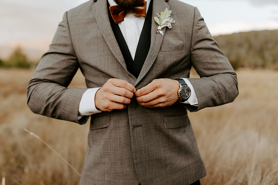 the groom in a café brown suit coat and blue pants with a gold velvet bow tie
