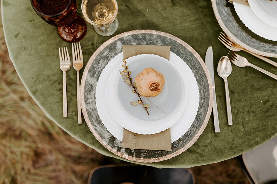 table with green linens with gold and white flatware