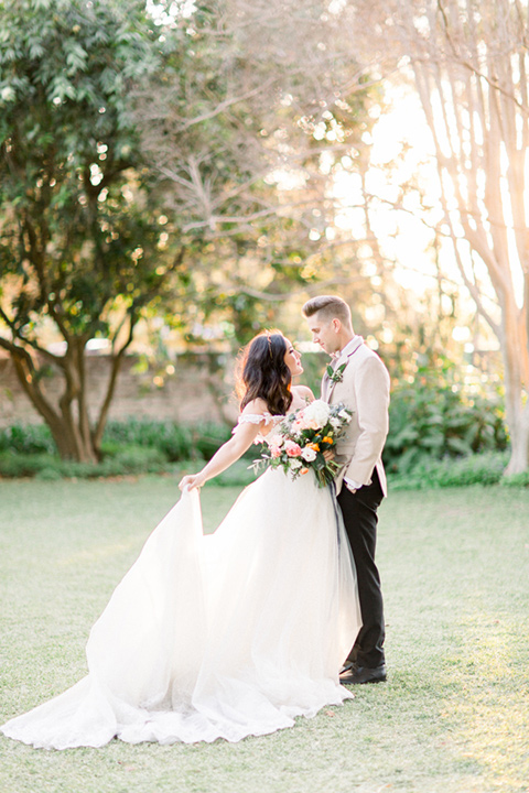 bride in a ballgown with a lace illusion neckline and long cathedral veil and the groom in a tan suit coat with black pants walking away