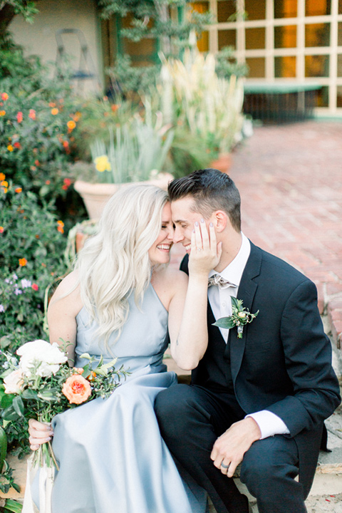 bridesmaid in a silver blue high low gown and the groomsman in a navy notch lapel suit