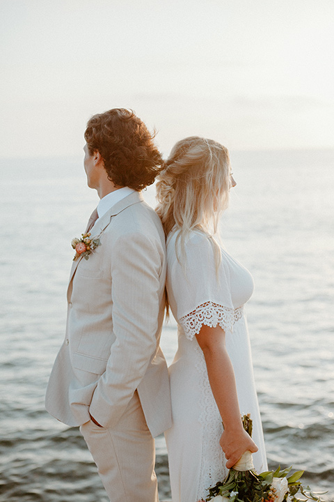 bride in a bohemian white lace gown and the groom in a light tan suit with a caramel long tie