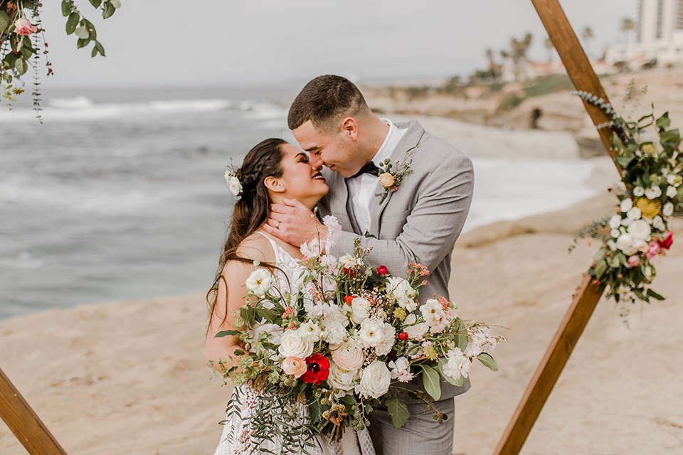bride in a white gown with a flowing white skirt and low cut back and the groom in a light grey suit and charcoal bow tie at the ceremony
