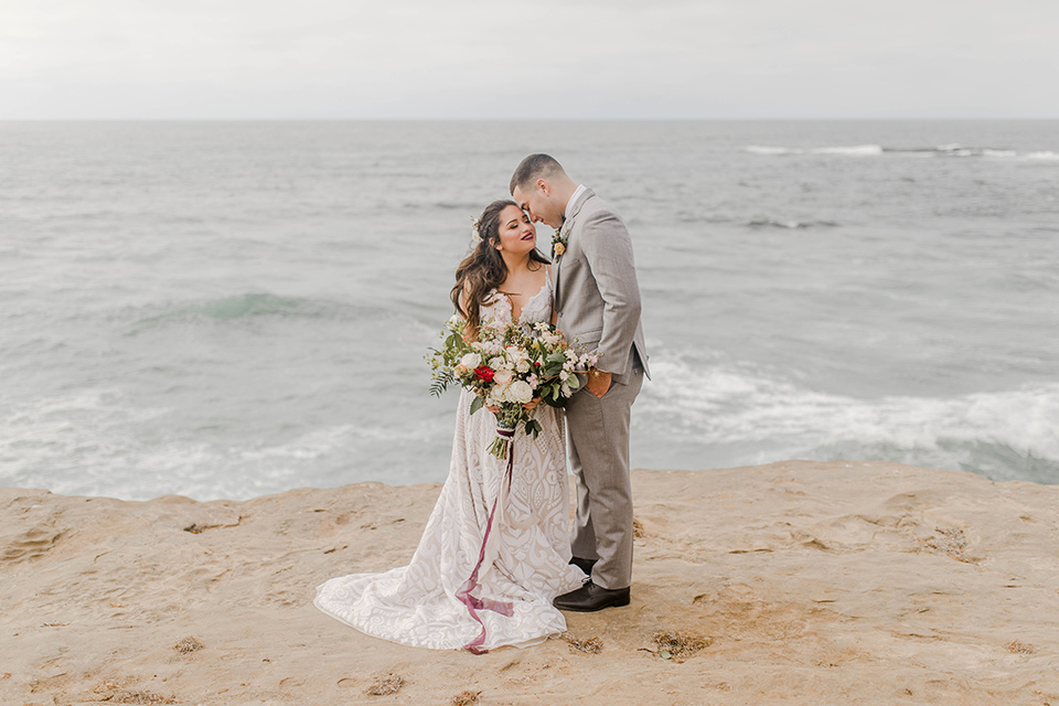 bride in a white gown with a flowing white skirt and low cut back and the groom in a light grey suit and charcoal bow tie near the beach