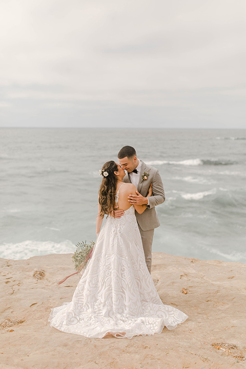bride in a white lace gown with a soft long skirt and a low cut back and the groom in a light grey suit with the charcoal grey bow tie