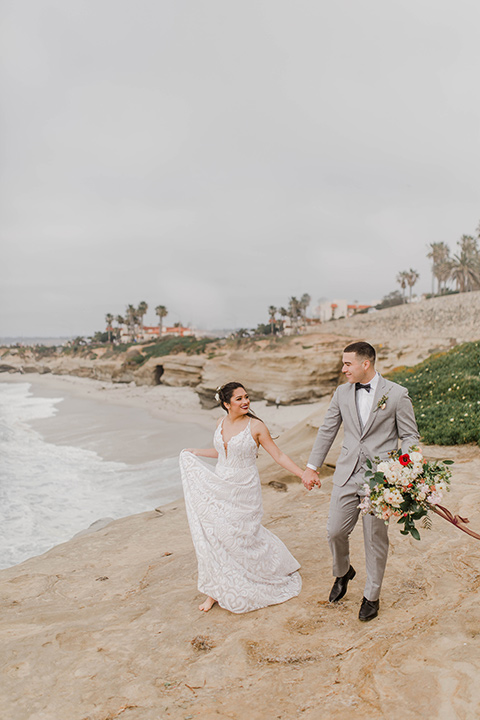 bride in a white flowing gown and a low cut back and the groom in a light grey suit with a white shirt and dark grey bow tie walking along the beach