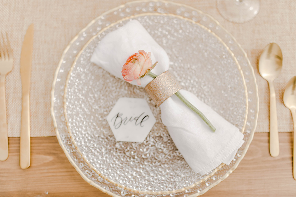 silver and white plates and linens with gold flatware