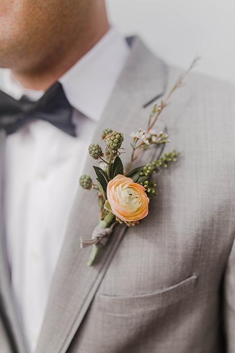 the groom in a light grey suit with a white shirt and dark grey bow tie