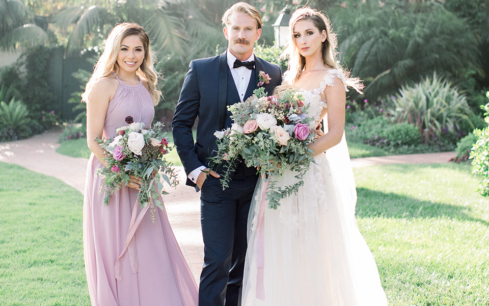 bride in a white gown with a lace and embellished design and long sleeves, the groom in a navy shawl lapel tuxedo and the bridesmaid in a rose pink long gown