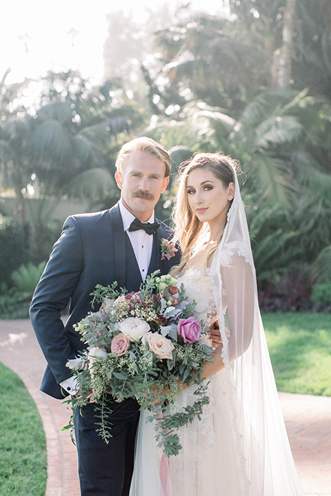 bridal gown with a lace and crystal design on it with long sleeves with the groom in a navy shawl lapel tuxedo with a black satin lapel outside