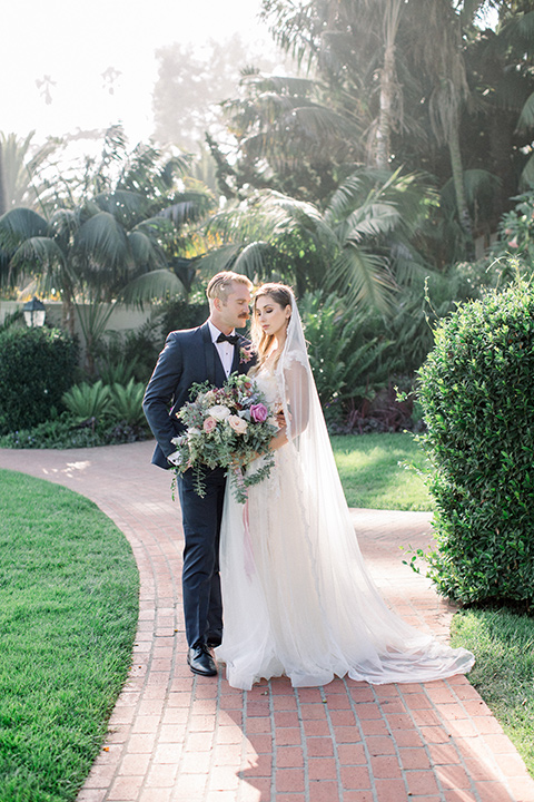 bridal gown with a lace and crystal design on it with long sleeves and the groom in a navy blue tuxedo shawl lapel tuxedo with a black bow tie, outside