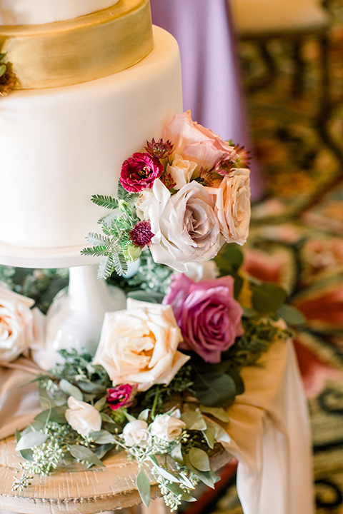 cake with white and gold fondant with floral decor