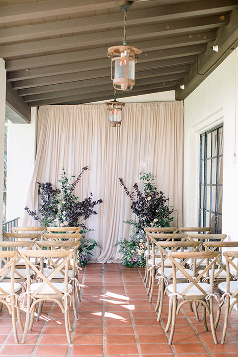 white chairs with purple and green floral arches
