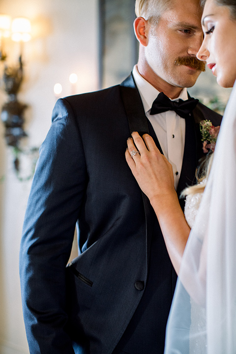 bridal gown with a lace and crystal design on it with long sleeves and the groom in a navy blue tuxedo shawl lapel tuxedo with a black bow tie close up