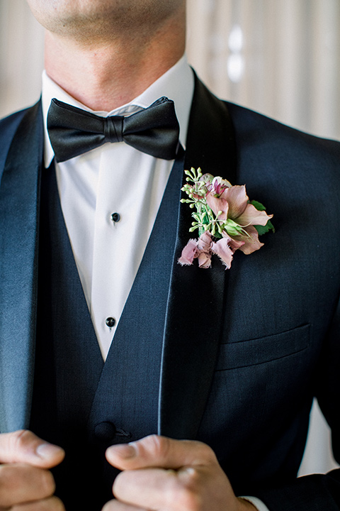 the groom in a navy blue tuxedo shawl lapel tuxedo with a black bow tie close up
