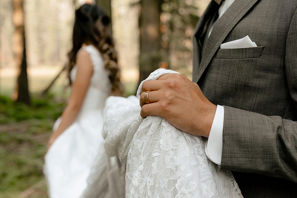 bride in a lace white gown with lace straps and a formfitting bodice and the groom in a café brown suit with a gold velvet bow tie
