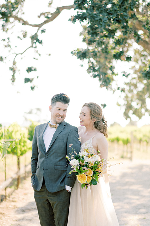 bride looking in a white flowing gown and the groom in a grey notch lapel suit with a gold velvet bow tie