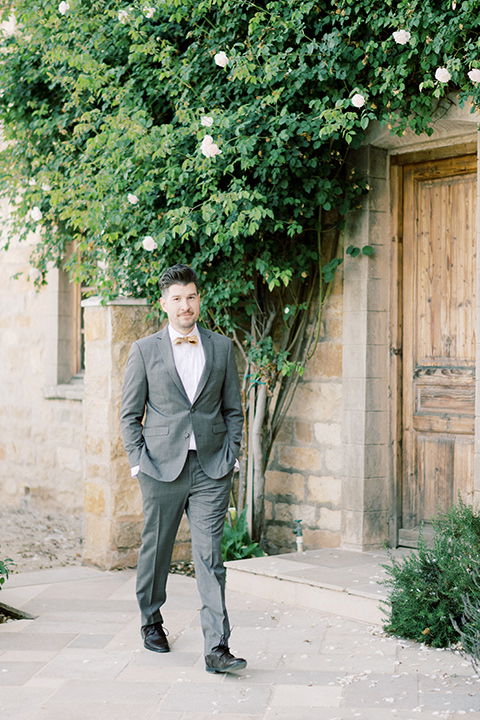 groom in a grey notch lapel suit with a gold velvet bow tie