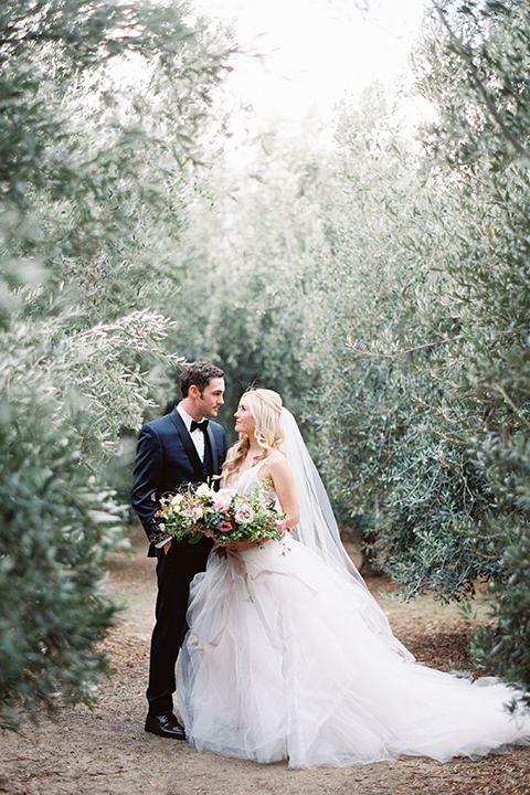 bride in a white ballgown with a tulle skirt and lace bodice detailing, the groom in a navy tuxedo with a black shawl lapel embracing