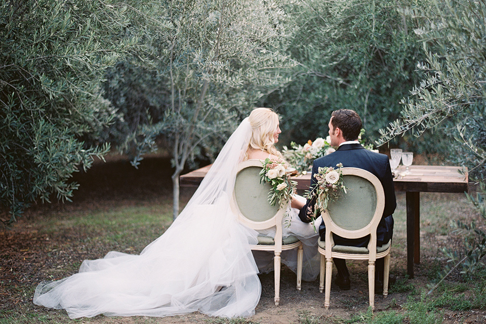 bride in a white ballgown with a tulle skirt and lace bodice detailing, the groom in a navy tuxedo with a black shawl lapel sitting at the sweetheart table