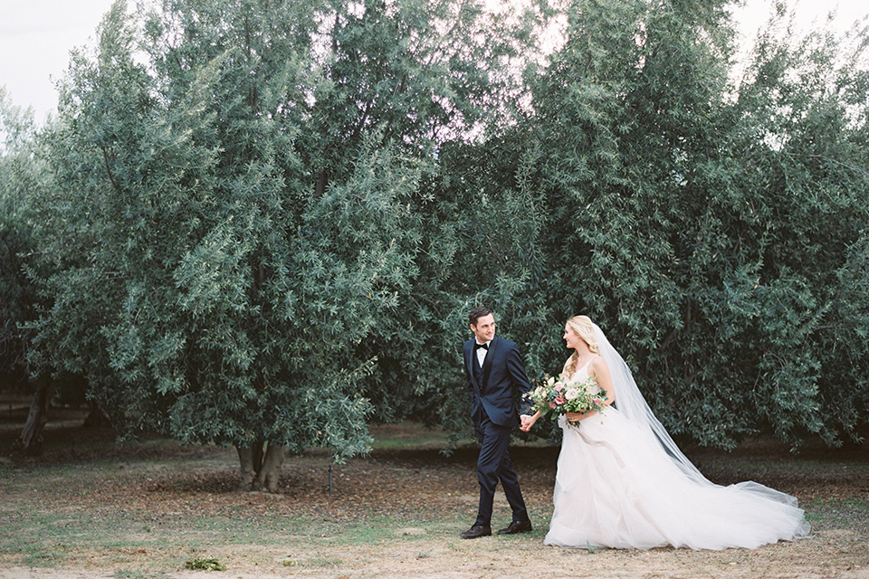 bride in a white ballgown with a tulle skirt and lace bodice detailing, the groom in a navy tuxedo with a black shawl lapel walking hand in hand