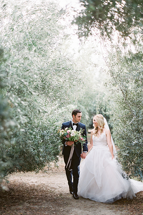 bride in a white ballgown with a tulle skirt and lace bodice detailing, the groom in a navy tuxedo with a black shawl lapel walking