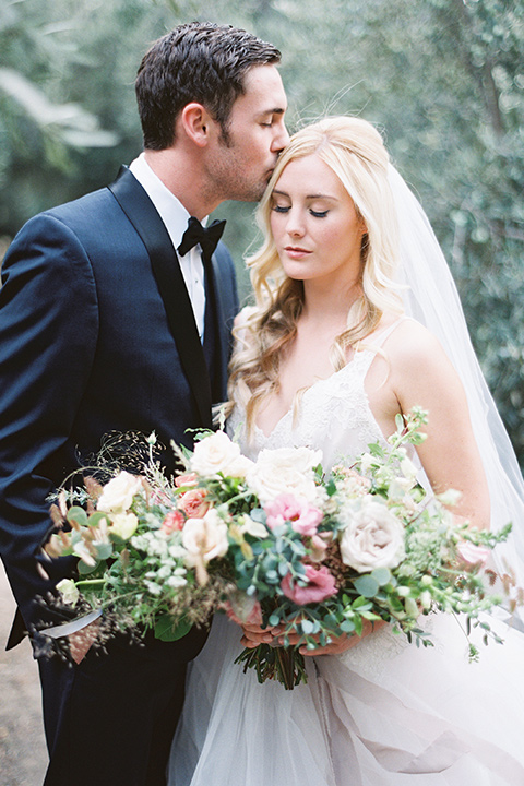 bride in a white ballgown with a tulle skirt and lace bodice detailing, the groom in a navy tuxedo with a black shawl lapel close together