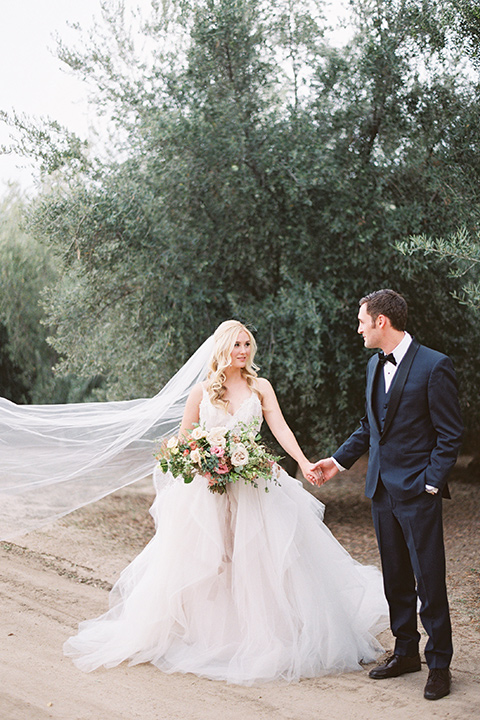 bride in a white ballgown with a tulle skirt and lace bodice detailing, the groom in a navy tuxedo with a black shawl lapel holding hands