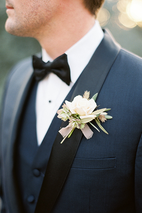 the groom in a navy tuxedo with a black shawl lapel close up