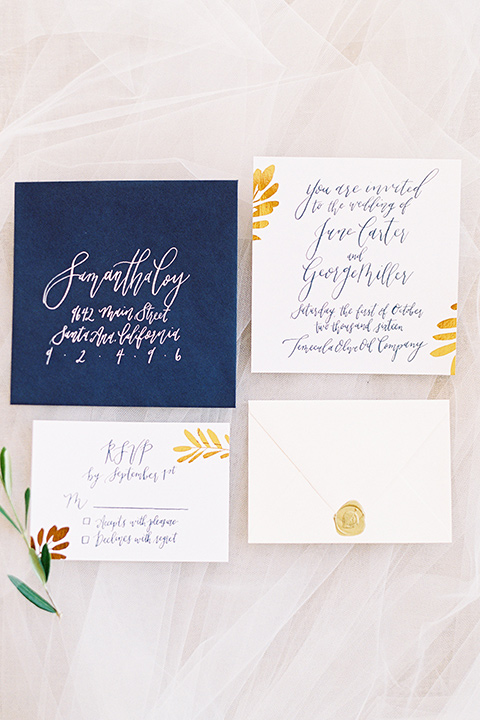 white invitations with blue envelopes and gold calligraphy